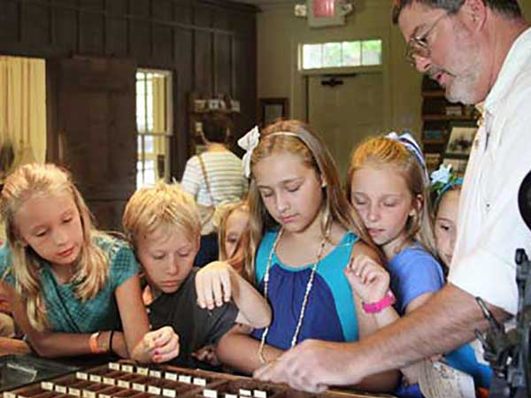 an image of several kids examining weaving loom