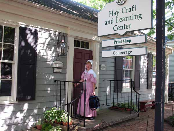 A costumed interpreter stands in front of the Hay Activity Center building